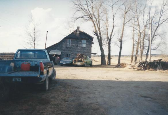 picker's truck pulled up to an old northern farm